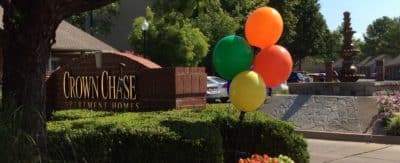 The brick sign for Crown Chase, with flowers and balloons in the foreground