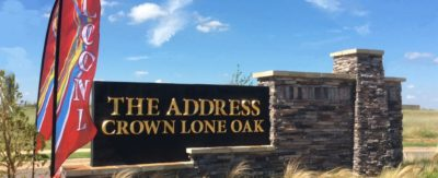 Gold lettering and colorful flags highlight the stone monument sign for Crown at Lone Apartments.