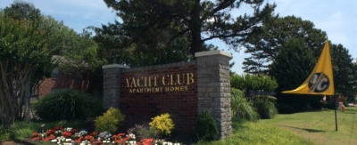 The monument sign at Yacht Club is surrounded by colorful flowers.